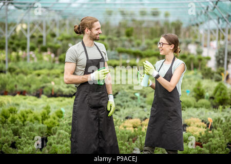 Young couple of workers having fun sprinkling water at the greenhouse of the plant shop - Stock Photo