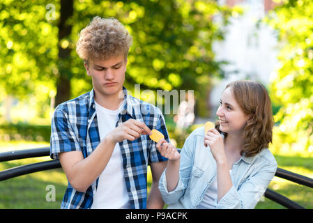 Young students in summer in a park outdoors. They sit on a bench in the city. Girl and happy smiling gives food to guy. The guy is embarrassed. The concept of mistrust. Emotion of kindness. - Stock Photo