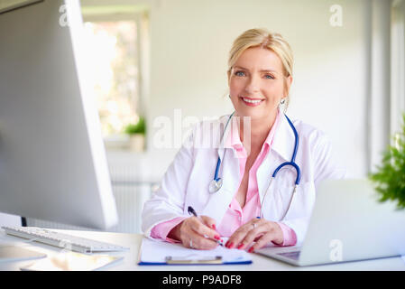 Close-up portrait of senior female doctor sitting at doctor's office at desk in front of laptop and doing some paperwork. - Stock Photo