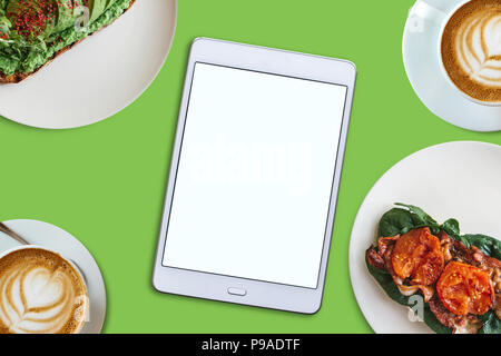 View from above. In the middle is a tablet with a blank screen for text. Next to him a variety of food and coffee. Food delivery or a cozy morning wit - Stock Photo
