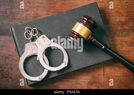 Law and order concept. Handcuffs, gavel on book on a wooden background, top view - Stock Photo