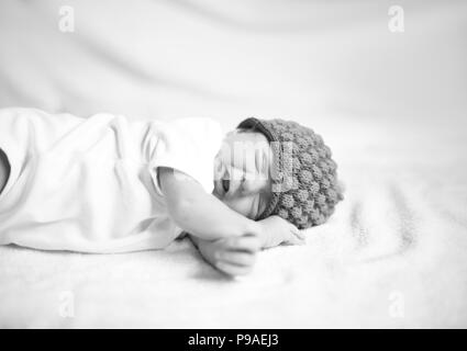 newborn baby in knitted hat lying on the white sheet. - Stock Photo