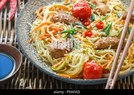 Stir fried noodle with chicken, vegetable (carrot, tomato,  zucchini, garlic, red pepper, green onion), sesame seeds and soy sauce on clay plate close - Stock Photo