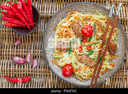 Stir fried noodle with chicken, vegetable (carrot, tomato, zucchini, garlic, red pepper, green onion), sesame seeds and soy sauce on clay plate. Asian - Stock Photo