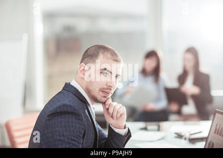 senior Manager at the workplace on the background of business team - Stock Photo