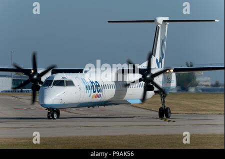 A Flybe Bombardier Dash 8 Q400 taxis along the runway at Manchester Airport whilst preparing to take off. - Stock Photo