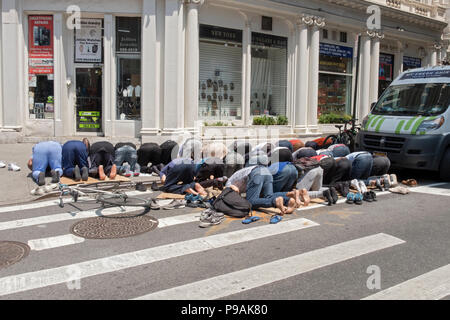 A group of Muslim men at their regular Friday afternoon prayer session on Broadway & West 29th Street in Manhattan, New York City - Stock Photo