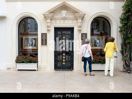 The exterior and entrance to Graff, a high end jewelry store on Worth Ave. in Palm Beach, Fl.. A security man stands in the doorway & two women browse - Stock Photo