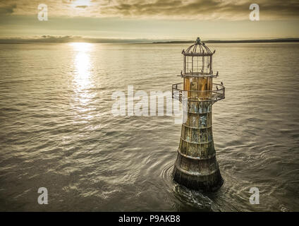 An aerial image of Whiteford Lighthouse at sunset. Now disused apart from it being a great rest stop for the local Cormorants. - Stock Photo