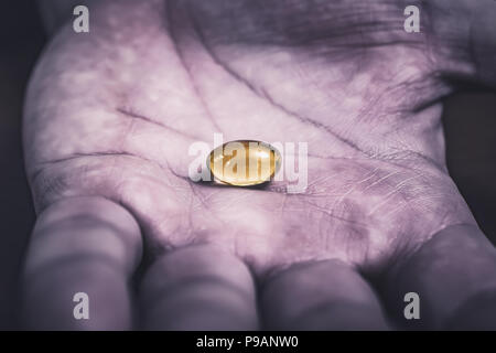 Gelatine Pill In The Middle Of A Dark, Dirty And Used Looking Hand, Top View - Stock Photo