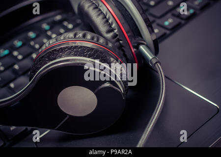 Small Black Wired Gaming Headset Lying On The Keyboard Of A Notebook - Stock Photo