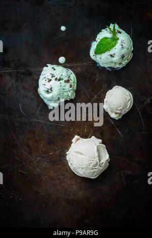 Selection of different ice cream scoops such as mint, chocolate and strawberry on dark background, top view - Stock Photo