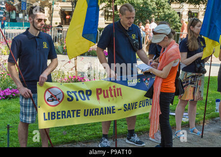 Helsinki, Finland. 16th July 2018. Ukrainan protesters with a banner at Esplanade Park in Helsinki during the Top Meeting of Trump and Putin Credit: Pekka Liukkonen/Alamy Live News - Stock Photo
