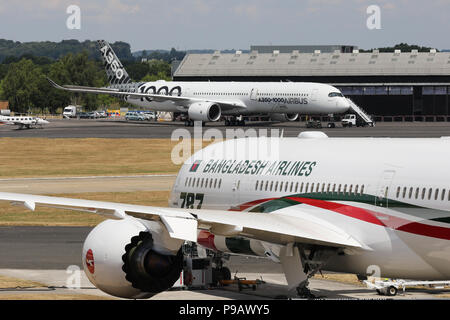 Farnborough, UK. 16th July 2018. A Boeing 787-800 of Bangladesh Airlines Biman, and an Airbus A350-1000 XWB test aircraft sit parked on the opening day of the 2018 Farnborough International Airshow, one of the biggest aviation trade and industry events in the world, held in the UK. Credit: James Hancock/Alamy Live News - Stock Photo