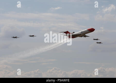 Farnborough, UK. 16th July 2018. Oil Spill Response organisation's Boeing 727 and The Blades aerobatic team perform a flypast on the opening day of the 2018 Farnborough International Airshow, one of the biggest aviation trade and industry events in the world, held in the UK. Credit: James Hancock/Alamy Live News - Stock Photo