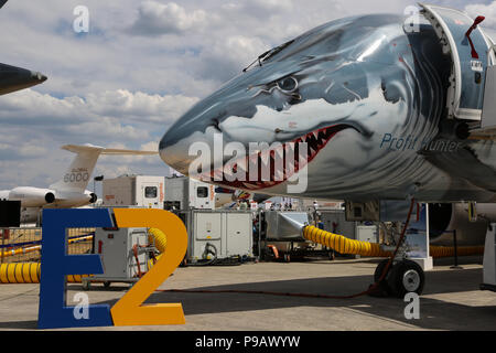 Farnborough, UK. 16th July 2018. An Embraer 190 E2 wearing a shark special paint scheme on the nose of the aircraft sits parked on the opening day of the 2018 Farnborough International Airshow, one of the biggest aviation trade and industry events in the world, held in the UK. Credit: James Hancock/Alamy Live News - Stock Photo