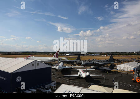 Farnborough, UK. 16th July 2018. A general view of aircraft from Boeing, Airbus, and Lockheed Martin which are parked at the end of the opening day of the 2018 Farnborough International Airshow, one of the biggest aviation trade and industry events in the world, held in the UK. Credit: James Hancock/Alamy Live News - Stock Photo