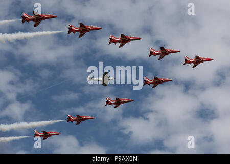 Farnborough, UK. 16th July 2018. The Royal Air Force Aerobatic Team, the Red Arrows, perform a flypast with a Supermarine Spitfire to open the 2018 Farnborough International Airshow, one of the biggest aviation trade and industry events in the world, held in the UK. Credit: James Hancock/Alamy Live News - Stock Photo
