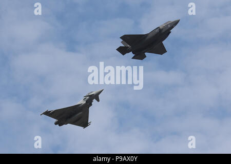 Farnborough, UK. 16th July 2018. A Royal Air Force Lockheed Martin F-35B and Eurofighter Typhoon perform a flypast on the opening day of the 2018 Farnborough International Airshow, one of the biggest aviation trade and industry events in the world, held in the UK. Credit: James Hancock/Alamy Live News - Stock Photo