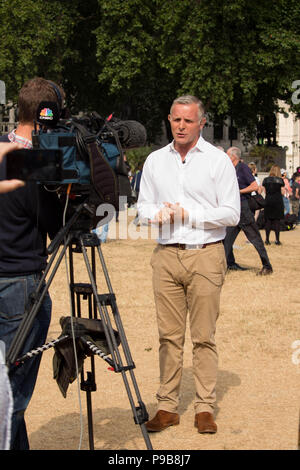 News reporter presenting coverage of 'STOP TRUMP' protest march in Parliament Square Gardens, London, UK 13/7/18. - Stock Photo