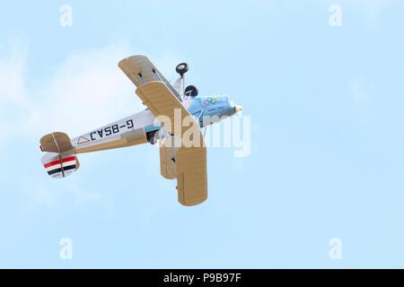German Bucker Jungmann bi-plane trainer flying inverted. G-BSAJ - Stock Photo