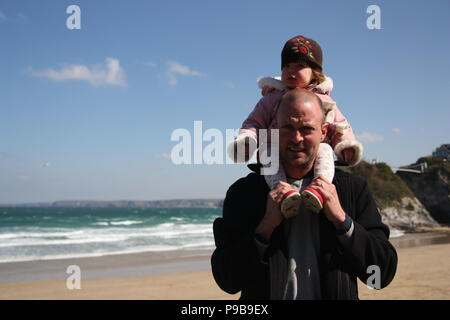 Man with young girl on his shoulder on a sandy beach at seaside Marazion Cornwall - Stock Photo