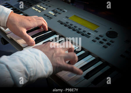 Closeup hands of musician playing synthesizer in concert - Stock Photo