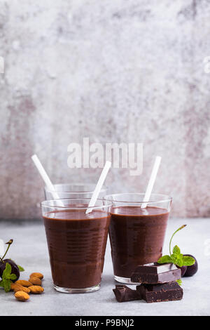 Chocolate smoothies with cherries and almonds. on a table of gray stone. Vegan protein drink for athletes and gourmets - Stock Photo