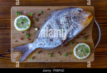 Fresh uncooked sea bream fish with lemon, herbs, pepper and spices on wooden cutting board and rustic table - Stock Photo