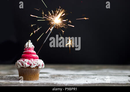 Cupcake with red swirl frosting and sparkler, christmas cupcake decoration - Stock Photo
