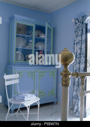 white chair and pale blue painted dresser in a pale blue bedroom rh alamy com