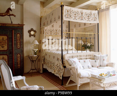 Floral patterned cream drapes with matching bed-cover on metal four-poster bed in Provencal bedroom - Stock Photo