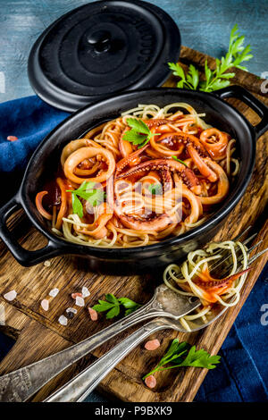 Italian cuisine, Calamari Fra Diavolo, spaghetti pasta marinara with seafood, light blue background copy space top view - Stock Photo