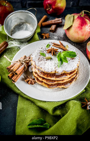 Sweet and spicy autumn apple pancakes, with anise, cinnamon and sugar, dark blue background copy space - Stock Photo