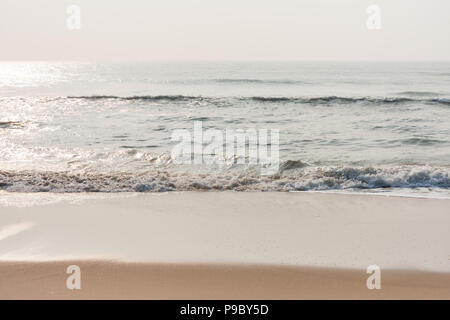 Glistening water on beach - Morning time on a tropical beach with glistening water and mild sea waves. - Stock Photo