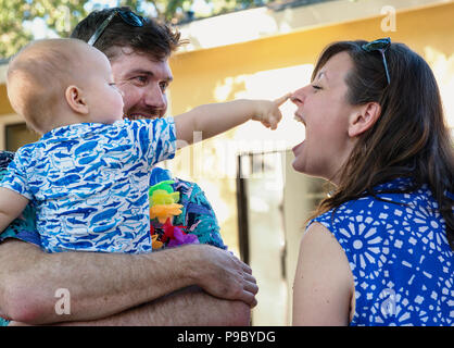 Parents and their baby hanging out at a backyard party. - Stock Photo
