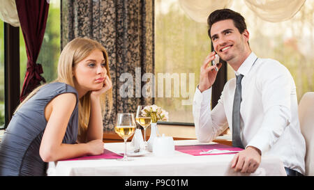 Woman is bored at restaurant, her boyfriend talks on the phone - Stock Photo