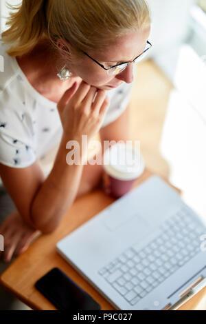 Woman using laptop online - Stock Photo