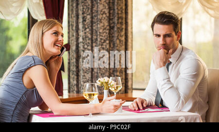 Man is bored at restaurant, his girlfriend talks on the phone - Stock Photo