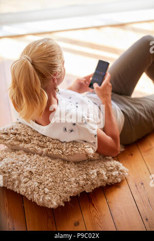 Woman laid on floor talking on her phone - Stock Photo
