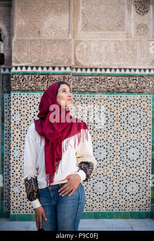 Muslim woman posing and looking up in traditional clothing with red hijab and jeans in front of traditional arabesque decorated wall - Stock Photo