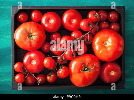 assorted tomatoes in wooden box - Stock Photo