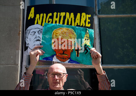 July 13th 2018.Central London. Demonstration against the visit of US President Donald Trump to England. A man holds a painting of Trump in front of an - Stock Photo