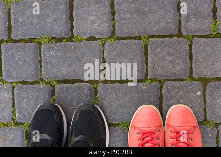 On the paving stones there are two pairs of shoes, top view - Stock Photo