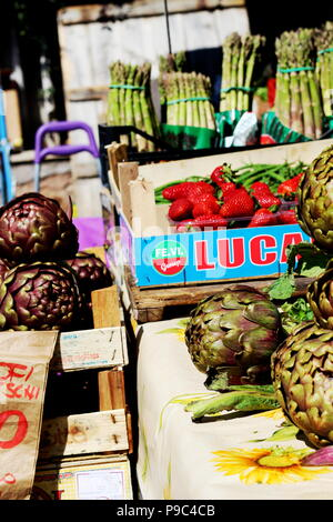 Artichokes, asparagus and strawberries on sale at a local fruit and vegetable market stall in Rome, Italy (Farmer's Market Via Urbano II) - Stock Photo