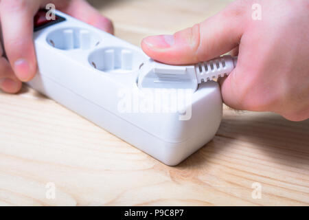 Pulling An Electrical Plug Out Of A Power Strip To Save Energy - Power Saving Concept