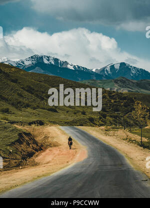 man on horse riding on Street in steppe with Tian Shan mountains in background, Kazakhstan Central Asia - Stock Photo