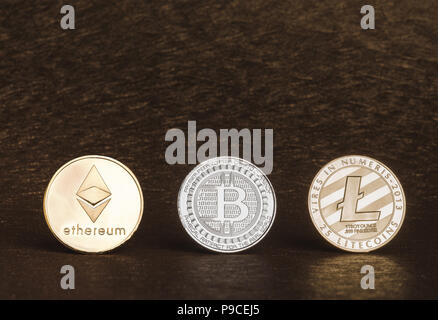 Cryptocurrency litecoin,Silver Bitcoin,Ethereum on golden rough background,Digital cryto currencies.Virtual money - Stock Photo