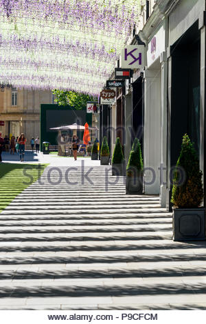 Street scene of a shopping mall with shadows cast on the ground from an imitation flower canopy above, Bath, Somerset, England - Stock Photo