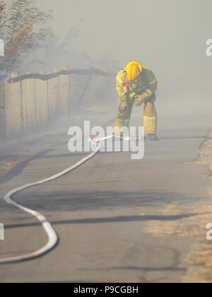 Melbourne, Australia - April 13, 2018: Fire fighter with a hose at a bush fire in an suburban area of Knox City in Melbourne east. - Stock Photo